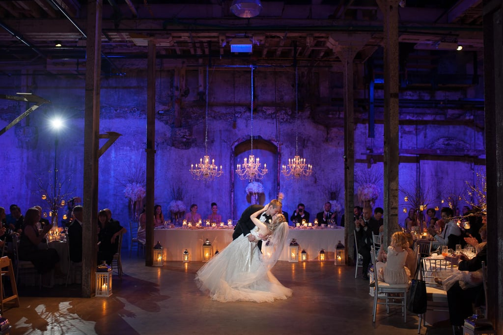 Cool uplighting candles and chandeliers warm up an industrial loft wedding reception
