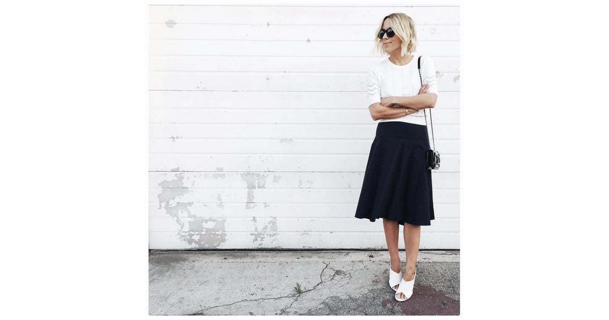 a white sweater black midi skirt and slip on shoes