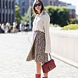 Tuck a long-sleeved button-down into your wrap skirt, and think bright when it comes to your bag and boots.
