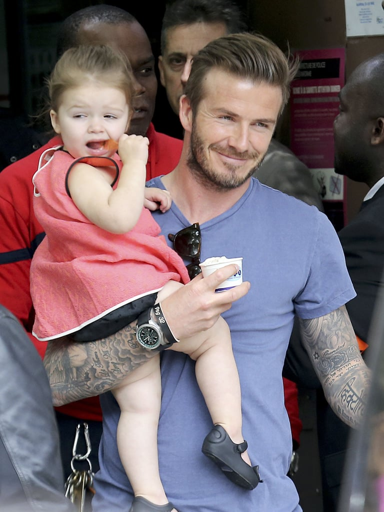 David was all smiles while carrying his daughter after they had a family lunch at the Eiffel Tower in May.