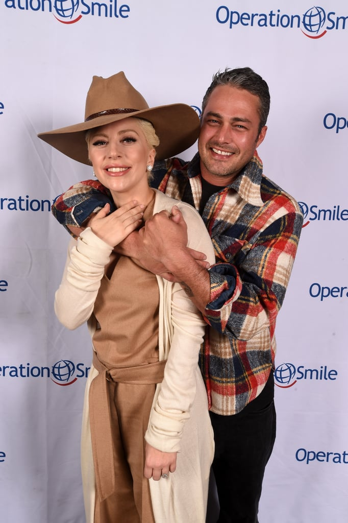 """Lady Gaga and Taylor Kinney packed on the PDA at Operation Smile's annual ski benefit in Park City, UT, on Saturday. The pair, who got engaged in February 2015, shared a series of sweet moments on the red carpet: Taylor wrapped his arms around Lady Gaga while she affectionately held his arm and smiled. In addition to helping raise money for Operation Smile, the duo posed for pictures with children and linked up with Ashlee Simpson and Taylor's brother Trent Kinney. Lady Gaga also took to Instagram the following day and uploaded shots from her snowy trip, along with an """"aw""""-inducing video of herself playing the piano while Taylor hugs her from the side. Keep reading to see more of Taylor and Lady Gaga, and then check out everything we know about their upcoming nuptials."""