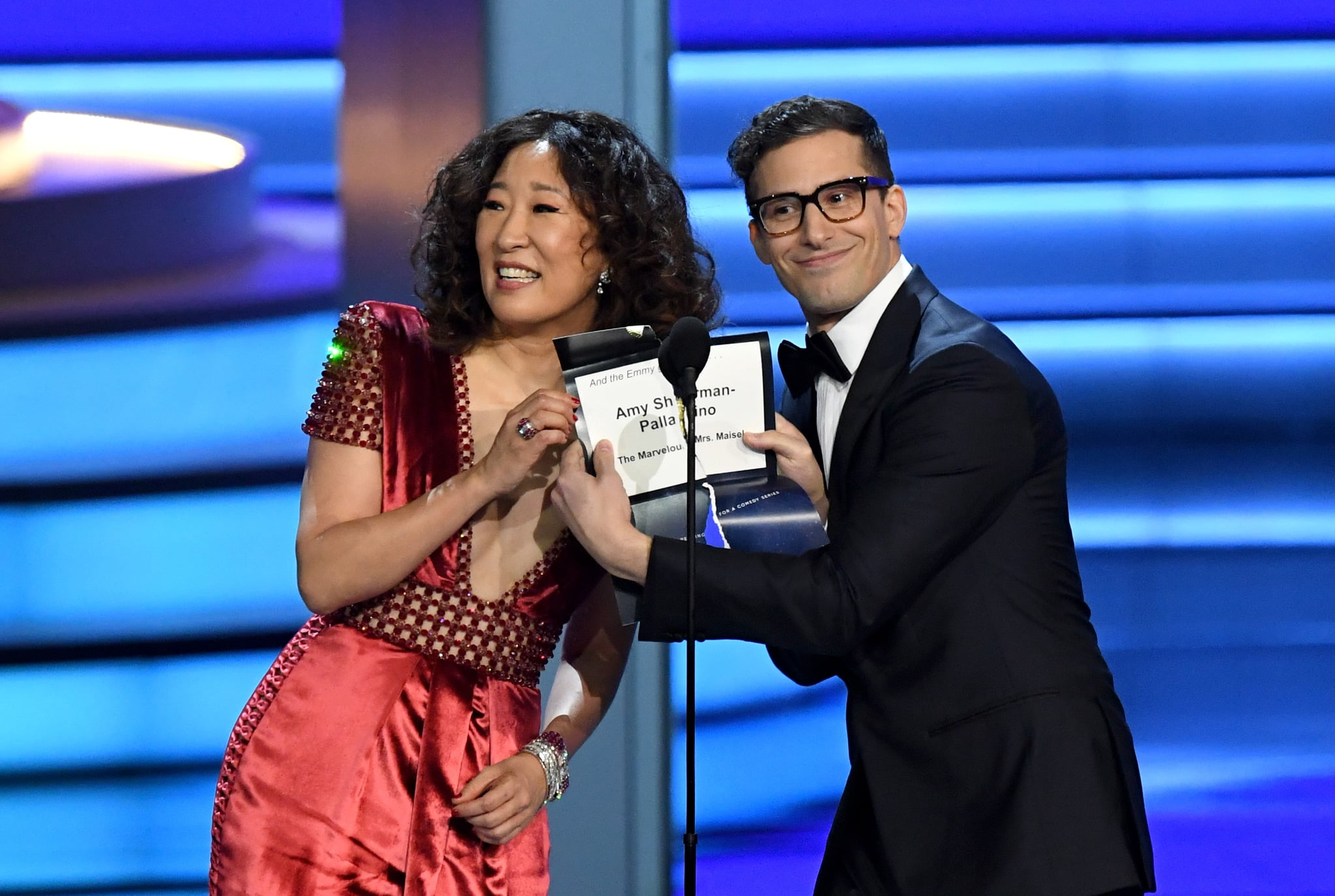 LOS ANGELES, CA - SEPTEMBER 17:  Sandra Oh (L) and Andy Samberg present the Outstanding Directing for a Comedy Series award onstage during the 70th Emmy Awards at Microsoft Theatre on September 17, 2018 in Los Angeles, California.  (Photo by Kevin Winter/Getty Images)