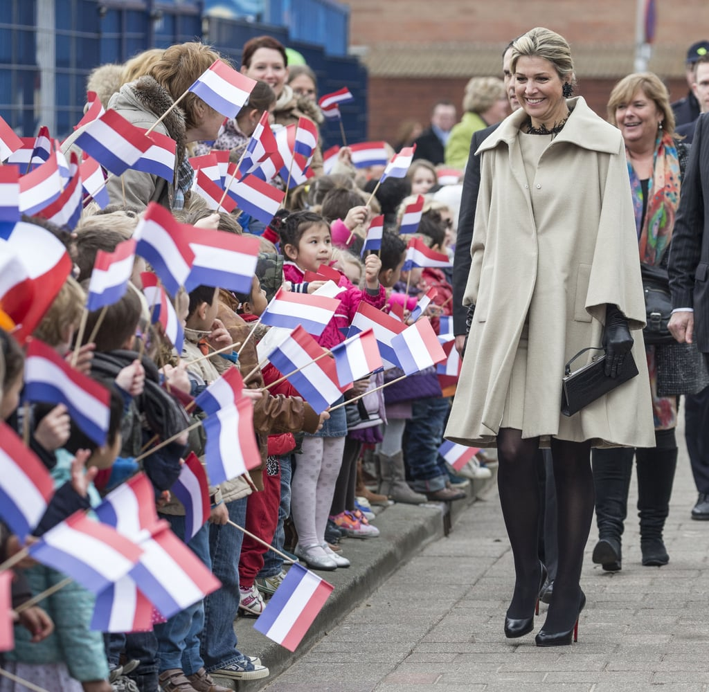 Queen Maxima of the Netherlands wearing a taupe cape coat.
