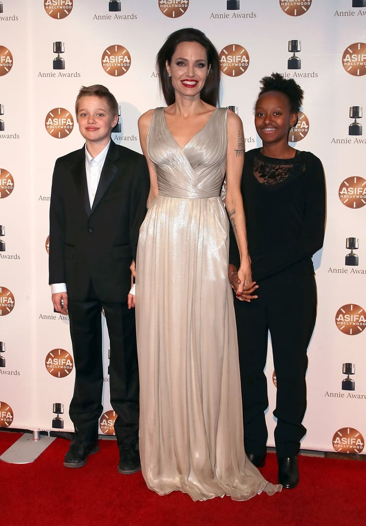Angelina Jolie had the unwavering support of two of her children while walking the red carpet at the 2018 Annie Awards in Los Angeles on Saturday night. The 42-year-old Oscar winner, who looked like a high-fashion princess in her silver Atelier Versace gown, brought 13-year-old Zahara and 11-year-old Shiloh Jolie-Pitt as her dates for the glamorous night out. Before heading inside to receive the award for best animated feature for the Oscar-nominated movie The Breadwinner, which she co-produced, Angelina and her daughters held hands and flashed big smiles in front of photographers. The UNHCR Goodwill Ambassador also struck a pose with The Breadwinner's director, Nora Twomey, and star, actress Saara Chaudry. This certainly isn't the first time Angelina has turned a glitzy Hollywood event into a family affair. The First They Killed My Father director took her 14-year-old son, Pax, as her date to the Golden Globes in January, and back in September she brought all six of her children — Maddox, Pax, Zahara, Shiloh, and twins Knox and Vivenne — as her dates to the Toronto Film Festival. In the wake of her tumultuous split from estranged husband Brad Pitt, it's clear that Angelina is putting her children first. Read on to see more photos from her, Shiloh, and Zahara's fun night out!      Related:                                                                                                           Angelina Jolie and Her Kids Get Cultured During a Family Museum Day in Paris
