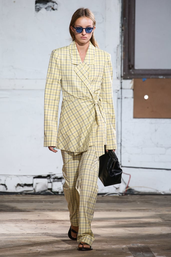 A model at the Tibi show pairing a black style with a plaid suit.