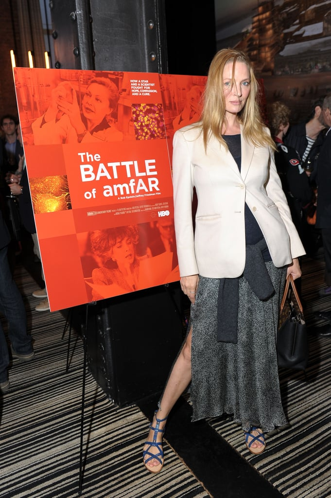 Uma Thurman was casual and cool in a maxi skirt featuring a side slit, a white blazer, a sweater that tied she around her waist, and blue metallic gladiator sandals.