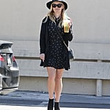 We love how Reese topped off her printed dress, black cardigan, and ankle booties with a wide-brimmed hat.