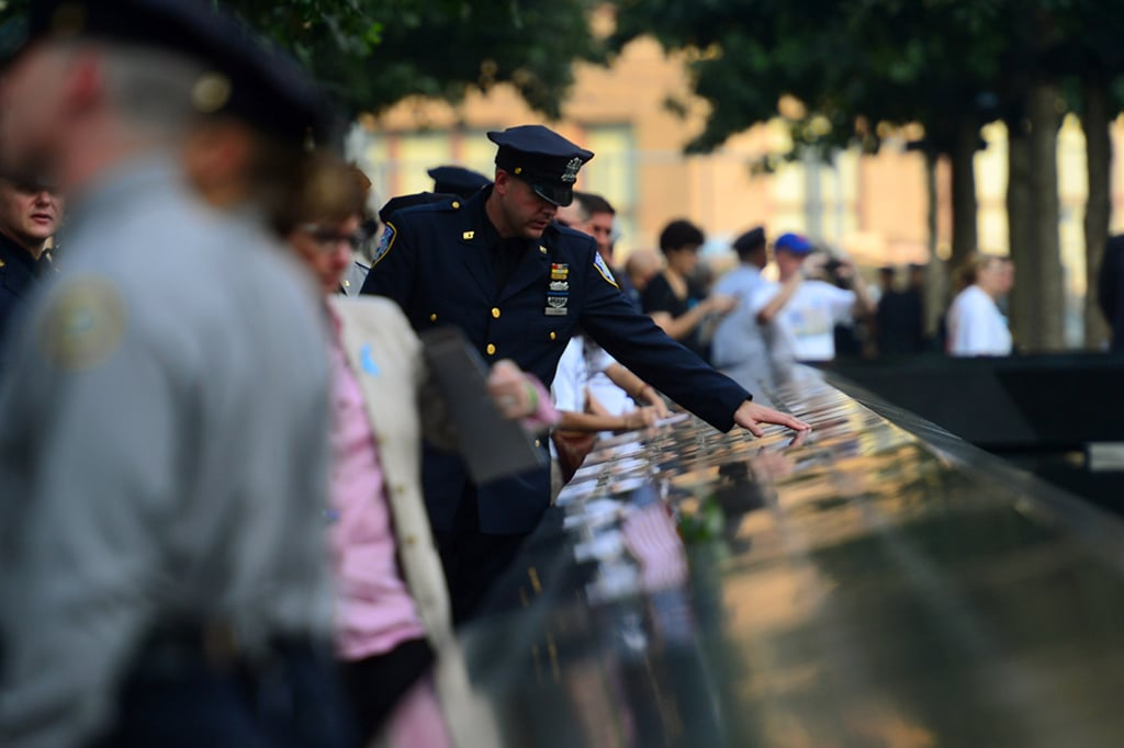 A police officer touched the 9/11 Memorial during the 12th anniversary ceremonies in NYC.