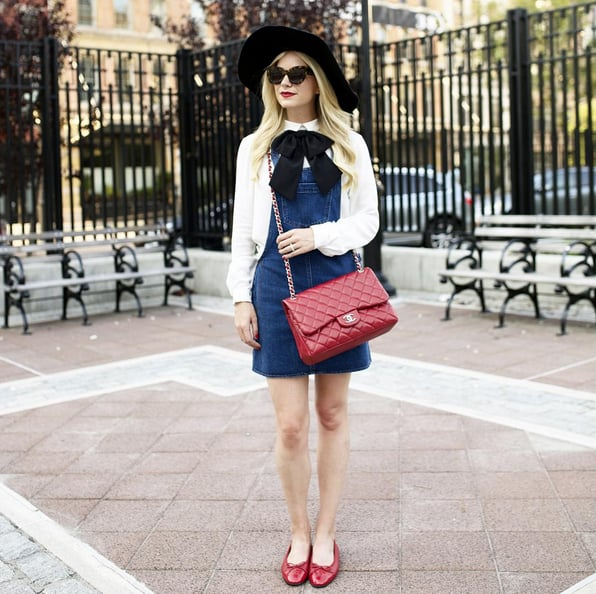 A Denim Overall Dress With a White Button-Down and Flats