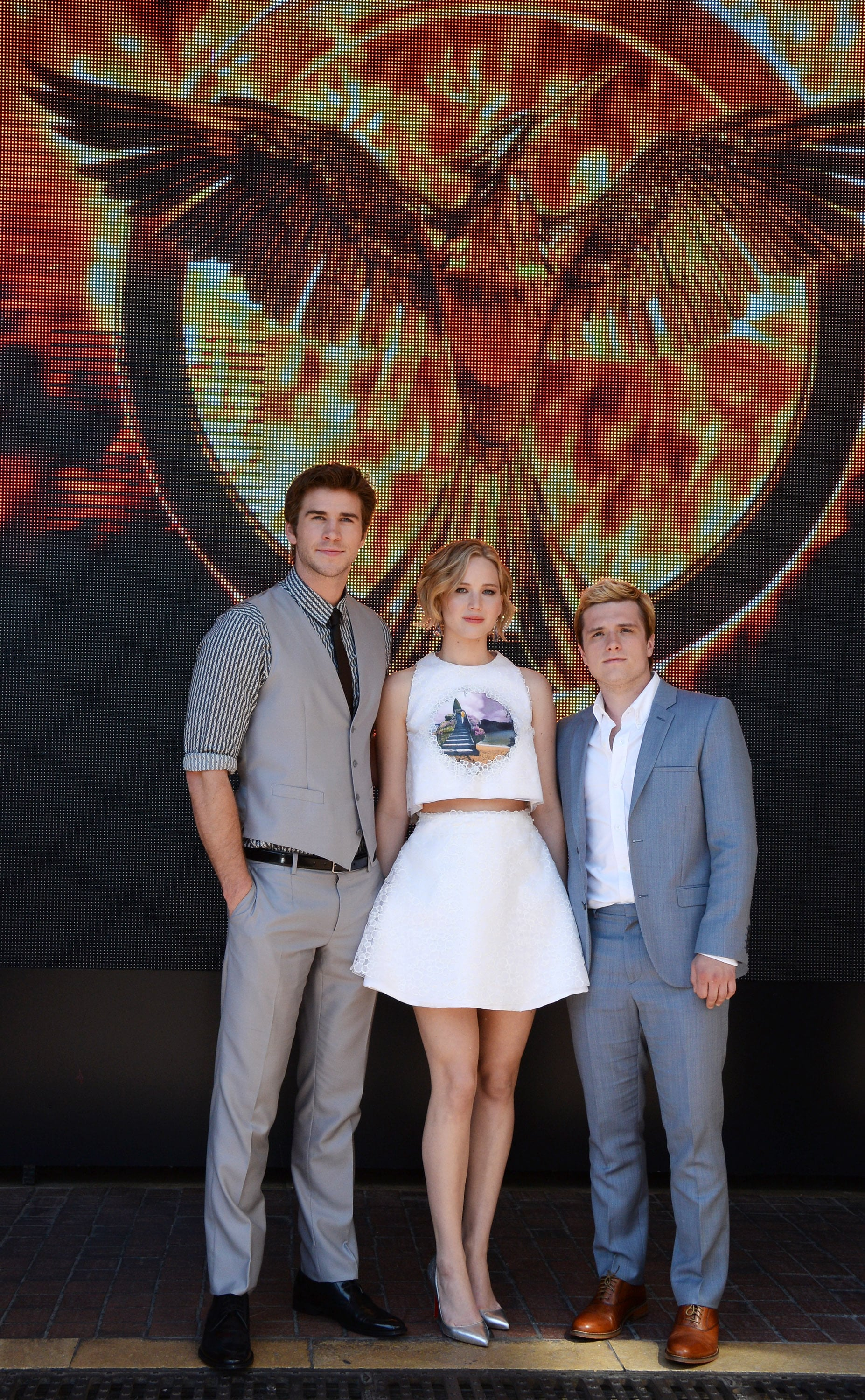 Liam Hemsworth, Jennifer Lawrence, and Josh Hutcherson stood in front of a giant Mockingjay backdrop.