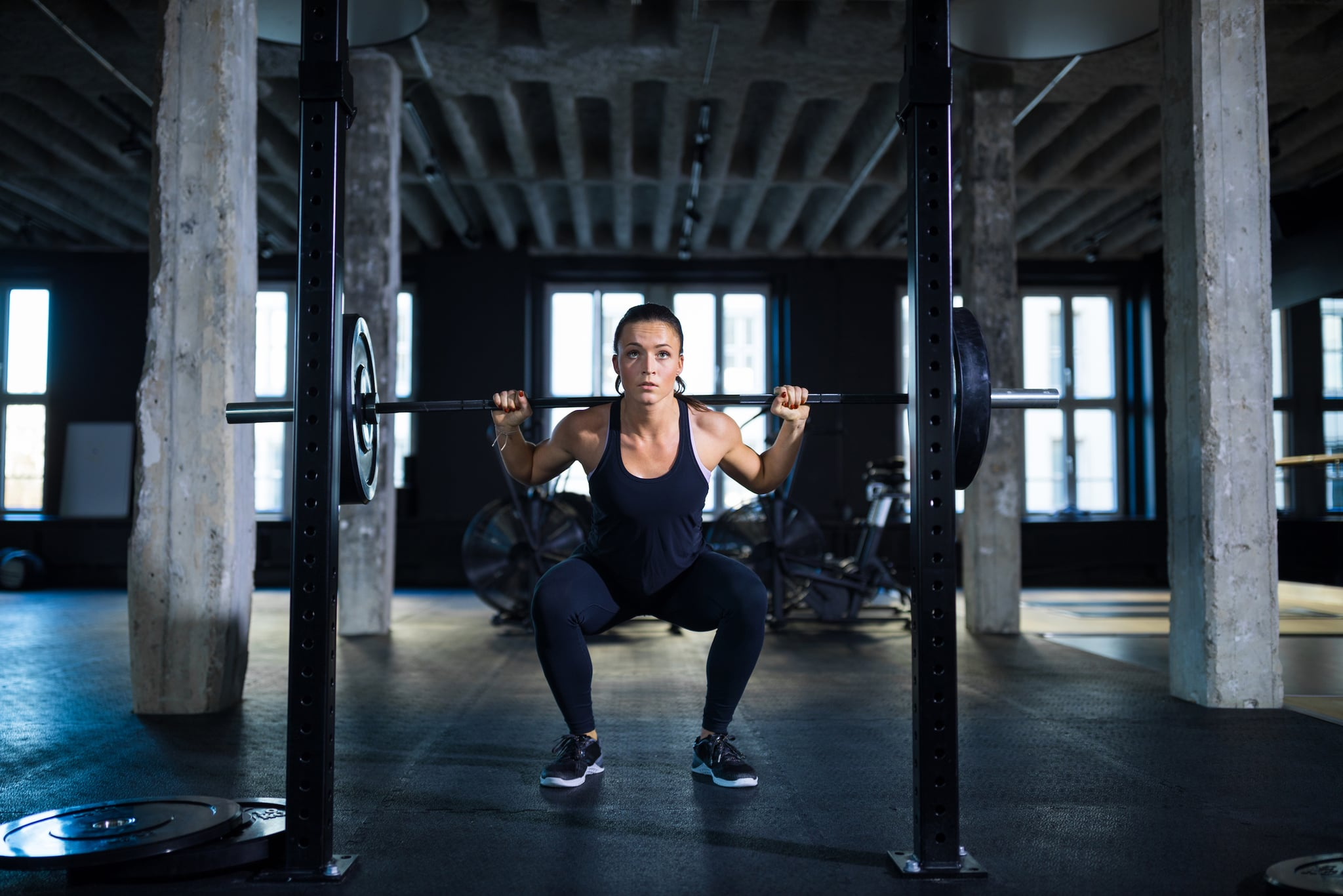 Determined woman crouching while exercising with barbell. Female athlete is working hard in gym. She is doing weightlifting.