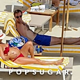 Pippa rubbed her belly as the couple relaxed on beach chairs.