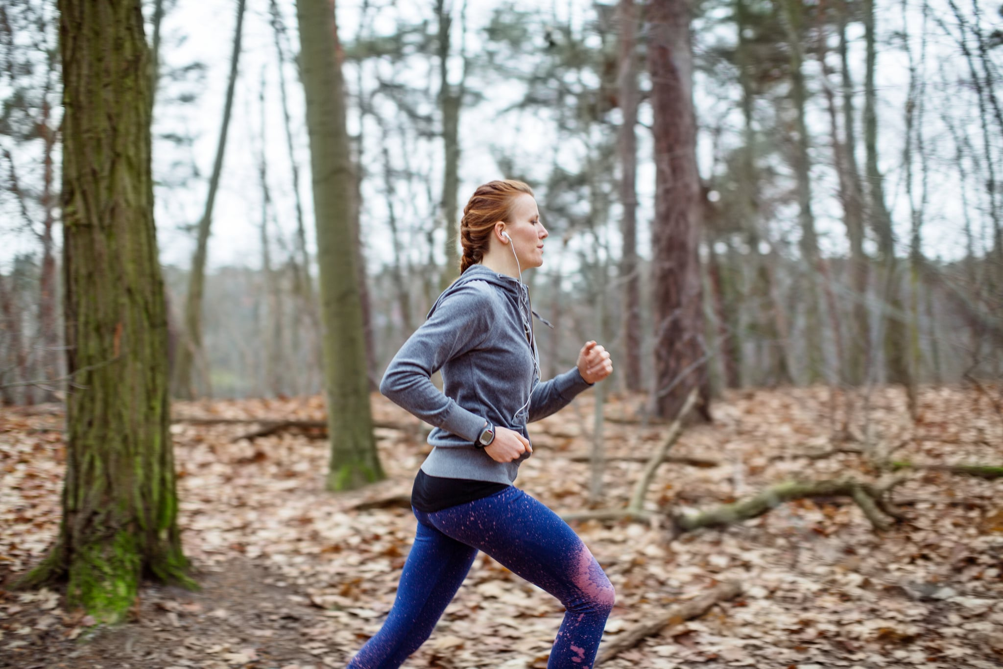 Side view of determined woman jogging in forest
