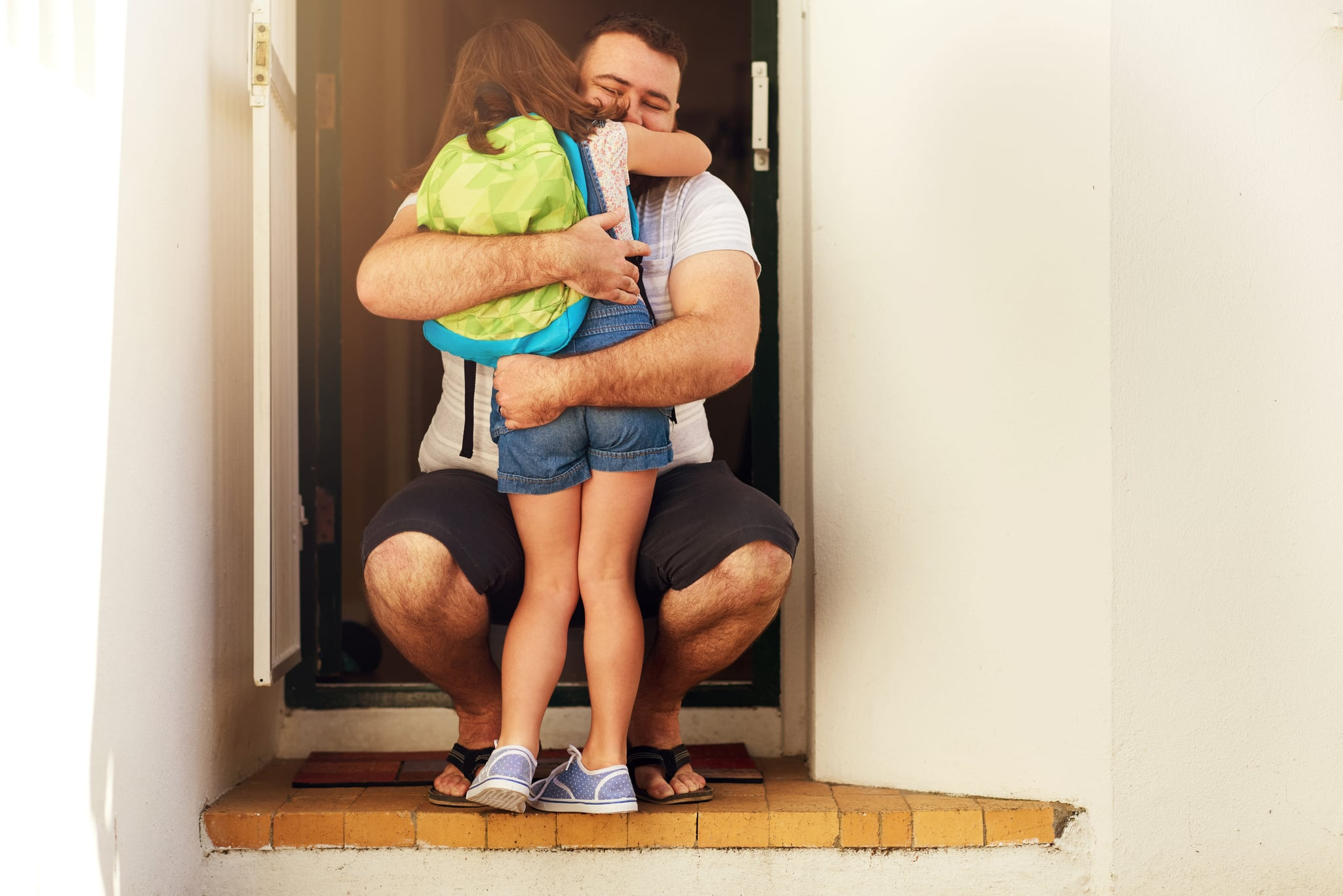 Shot of an adorable little girl hugging her father at the front door