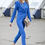 A neutral-toned clutch tempers the brilliant blue suiting.