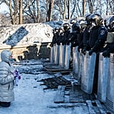 A woman spoke with police offers while kneeling in the snow.