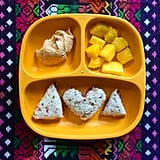 """""""Lunch: sunflower butter and jam sandwich on whole grain bread, red bell pepper hummus, and mango."""""""
