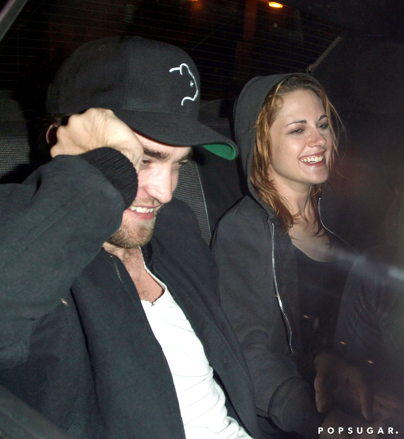 Robert Pattinson and Kristen Stewart shared a laugh and linked arms as they rode in a taxi together after a night out in LA in October 2010.