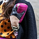 A pop of fuchsia on her clutch that looked like it could have been cut from the same fabric as her skirt.