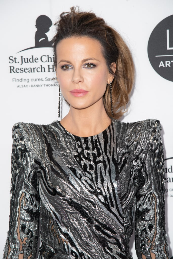 While most of us put our hair in a ponytail for trips to the gym or casual days spend chilling out at home, Kate Beckinsale has turned the style into her red-carpet trademark and worn it to all manner of high-profile events, from the Oscars to the Grammys. But these ponytails are anything but basic. With added teasing, curls, and copious extensions for volume, Kate's modern updos definitely take the ponytail to the next level. From sleek styles with cheerleader-esque curls to messy, modern textured looks, she and her hairstylist constantly find new twists on the look. Pulling the hair off the face makes the most of Kate's incredible bone structure and injects a fun, youthful element into her red-carpet style. Over the years, she has made this look her own, and we love every twist on the look, from the fun flipped-over pony to the sexier bouffants with loose strands around the face. Take a look at just a few of Kate's best hair moments now. Maybe they'll persuade you to try a formal ponytail in the future?