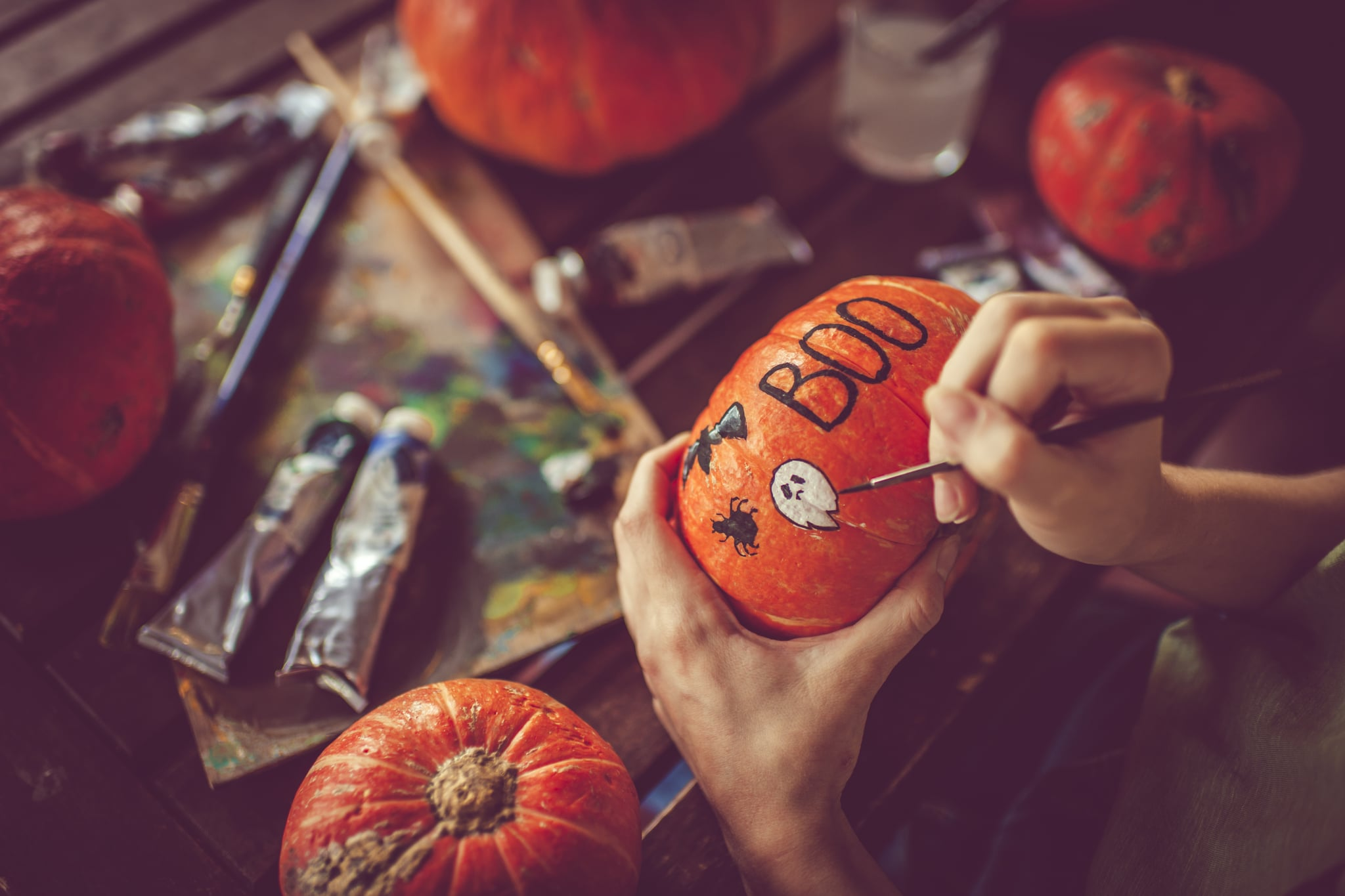 Woman painting on pumpkin preparing to Halloween in autumn
