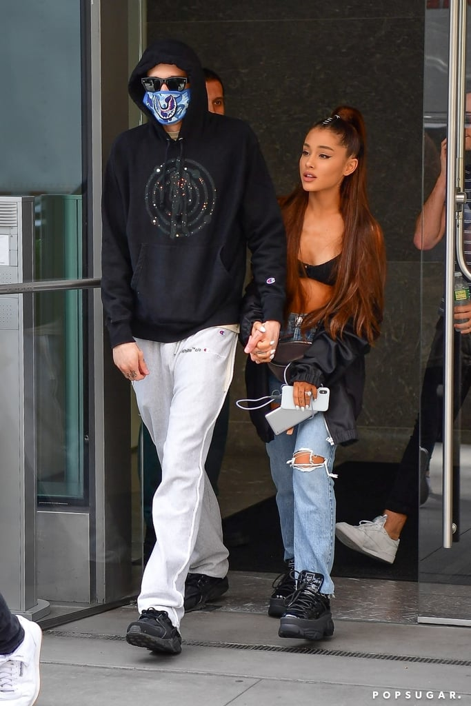 "The world can't stop keeping track of Ariana Grande and Pete Davidson's romance, and neither can we. The newly engaged couple was spotted walking hand in hand out of their NYC apartment. For their day date, the ""No Tears Left to Cry"" singer ditched her shirt for something a little more revealing.  Ariana styled what looked like either a black bra or bikini top with a bomber jacket that was left open. Recently, tons of celebrities have been wearing their swimsuits on the street. To tie her look together, the starlet styled her daring ensemble with a pair of high-waisted jeans and chunky platform sneakers. Pete, on the other hand, styled his hoodie and sweats with an interesting blue mask. Read on to get a closer look at Ariana's sultry look, and buy similar versions of her top ahead.      Related:                                                                                                           14 Moments in Ariana Grande and Pete Davidson's Relationship That Prove When You Know, You Know"