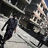 A White Helmet walks through damaged buildings following an airstrike in Douma.