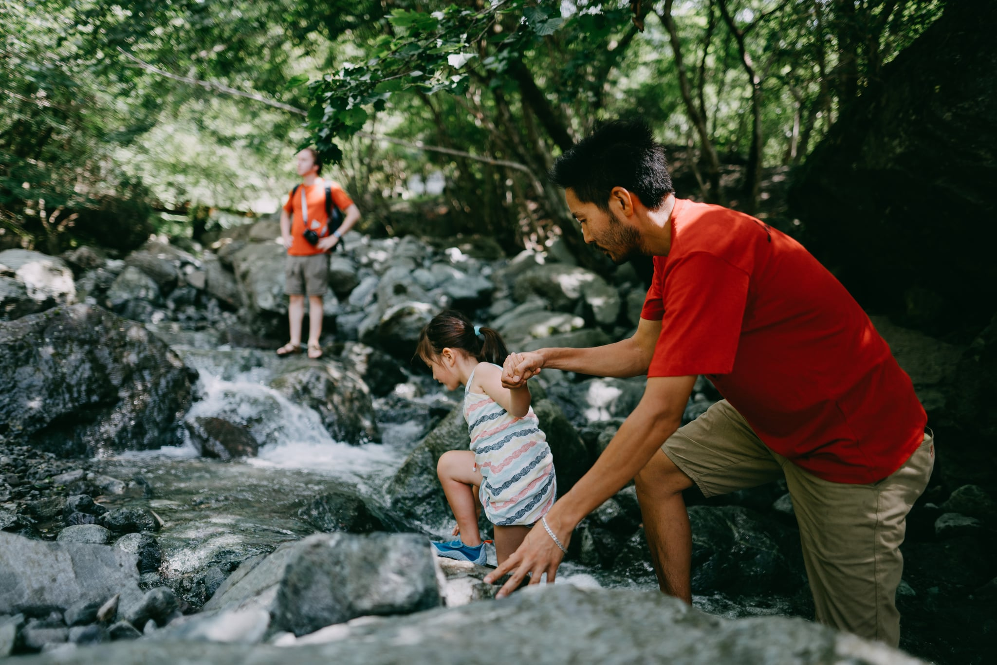 Japanese father and his mixed race little girl hiking in river, Japan