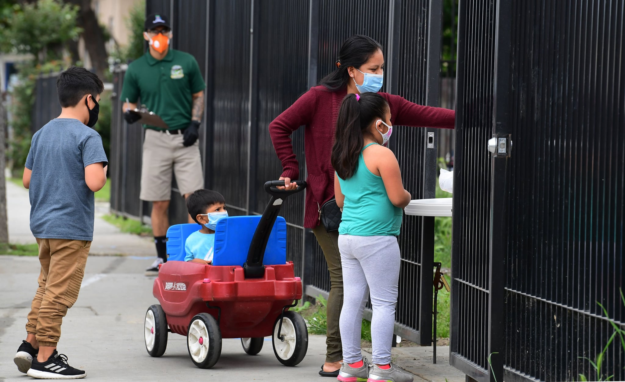 A woman with her children wearing masks, reaches out to pick up a bag of groceries distributed at a food bank opened in response to the coronavirus pandemic on April 20, 2020 in El Monte, California (Photo by Frederic J. BROWN / AFP) (Photo by FREDERIC J. BROWN/AFP via Getty Images)