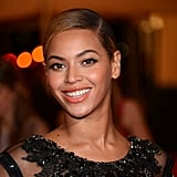 At the 2012 Met Gala, Beyoncé was the quintessential glamour girl. She paired her slicked-back style with dramatic eye makeup and glossy orange lips.