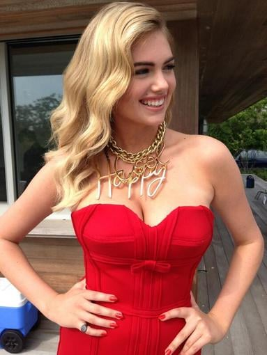 "Kate Upton looked sexy on the set in a tight red dress and ""Happy"" gold chain necklace. Source: Twitter user KateUpton"
