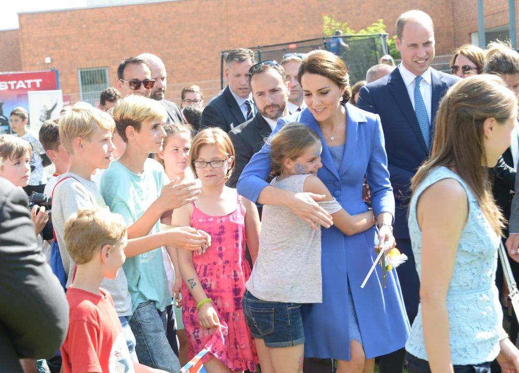 Following their whirlwind visit to Poland, the British royal family kicked off the second part of their latest tour when they landed in Germany on Wednesday. While Princess Charlotte and Prince George's cute antics were in full effect, Kate Middleton also had a few special moments of her own. During a stop at Strassenkinder, a charity that supports kids from disadvantaged backgrounds, Kate broke protocol when she greeted a group of kids with warm hugs. Royal etiquette states that greetings should not go beyond a handshake, but the family breaks this rule all the time, especially when emotion takes over. In fact, Prince William grabbed headlines just last month when he bent the rules to console a victim of the Grenfell Tower Fire.
