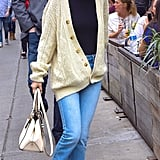 Selena styled an oversize cardigan with gold buttons with a dark turtleneck, Alice + Olivia distressed jeans, and black Tod's loafers.