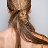 For an undone look like this one spotted backstage at the Josie Natori runway show, pull hair into a low ponytail, fold half of it up towards the base, and wrap a small section of hair around the loose ends. Then, secure with a bobby pin for extra hold.