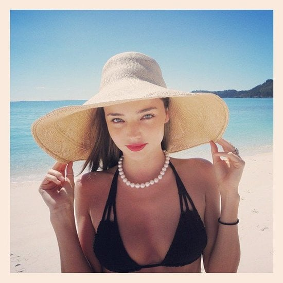 Smart lady! Miranda Kerr protected her skin by keeping under a large sun hat during a day on the beach.