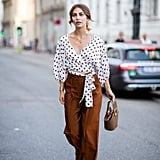 A polka-dot top feels playful with trousers and a unique bag.