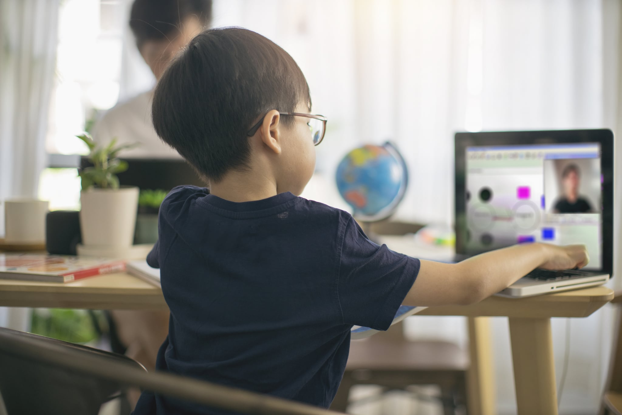Young boy home schooling along side with work from home father.