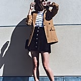 A camel-colored coat over a striped tee, suede skirt, and a pair of mules.
