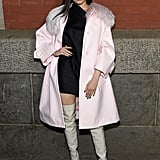 Wearing a pink wool coat by Marc Jacobs with over the knee boots and a black dress at the Marc Jacobs show during New York Fashion Week in February 2018.