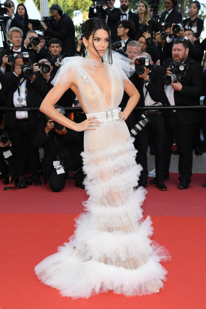 It looks like Kendall Jenner packed only sheer dresses for her trip to the Cannes Film Festival. The supermodel, who also rocked a glamorous high-leg swimsuit, started off her trip wearing a shimmery see-through minidress at an event for Chopard, but that's not all. Kendall also ditched her bra for the premiere of Girls of the Sun. The leggy model wore a super-sheer gown by Schiaparelli. The daring tulle dress featured a plunging neckline with a tiered skirt and ruffled shoulders. Kendall accessorized with a matching belt, a diamond seahorse pin, and a pair of Chopard statement earrings. Keep reading to see all angles of her NSFW gown.      Related:                                                                                                           What Shocks You More: Kendall Jenner's Plunging Suit or Glow-in-the-Dark Mules?