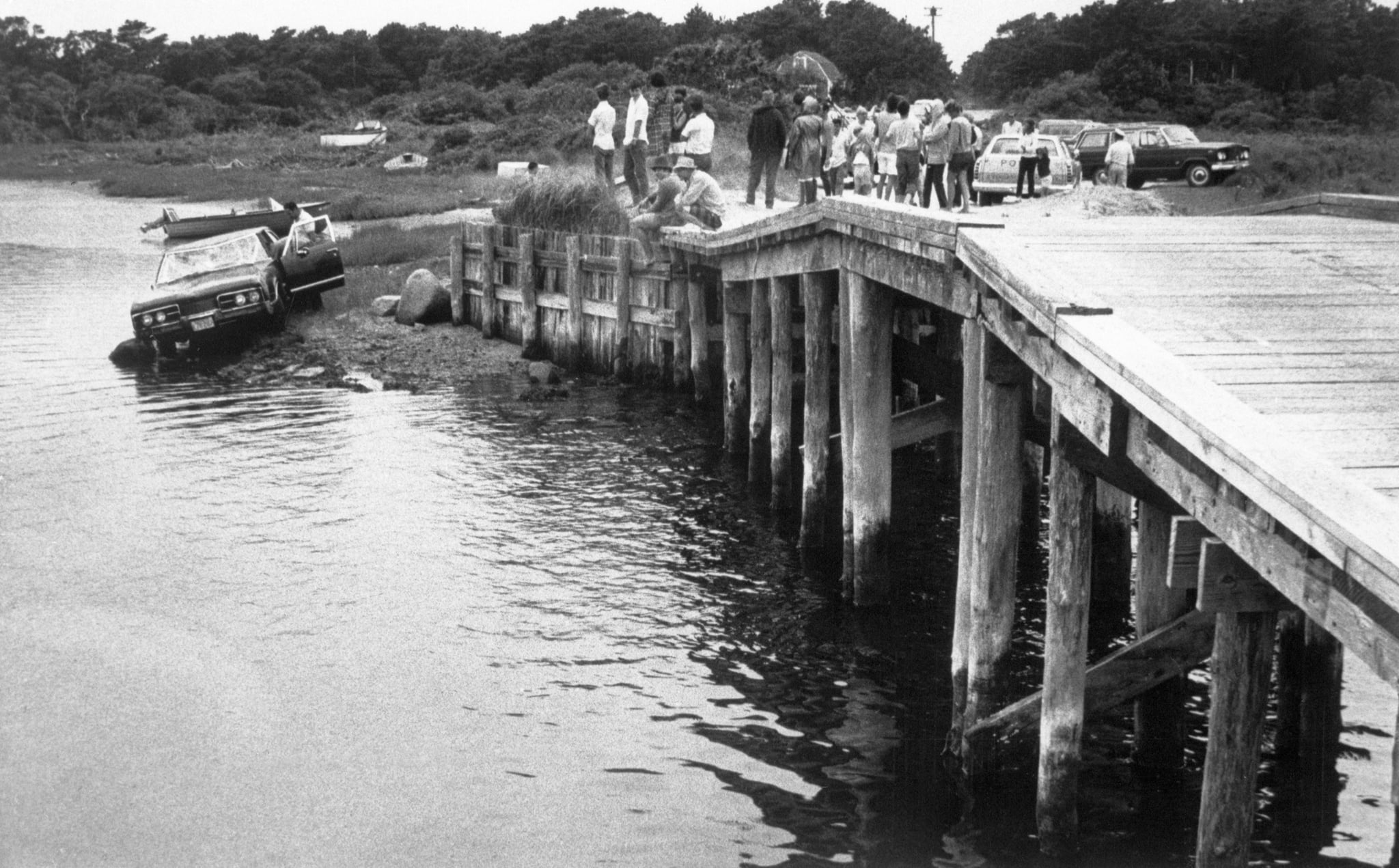 (Original Caption) 7/24/1969- Edgartown, MA- Curious spectators look on from pier at the car driven by Massachusetts Senator Edward Kennedy which plunged off a bridge on Martha's Vineyard on July 19th. Kennedy escaped from the crash in which Miss Mary Jo Kopechne, 29, of Washington, DC, was killed. She had worked as a secretary to the late Senator Robert Kennedy. BPA2#4587.