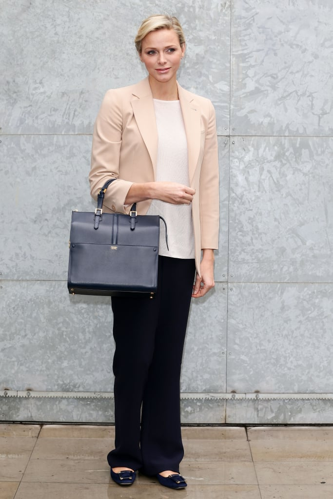 In February 2013, Princess Charlene wore black pants with a white tee, blush blazer, and flats to the Giorgio Armani show.