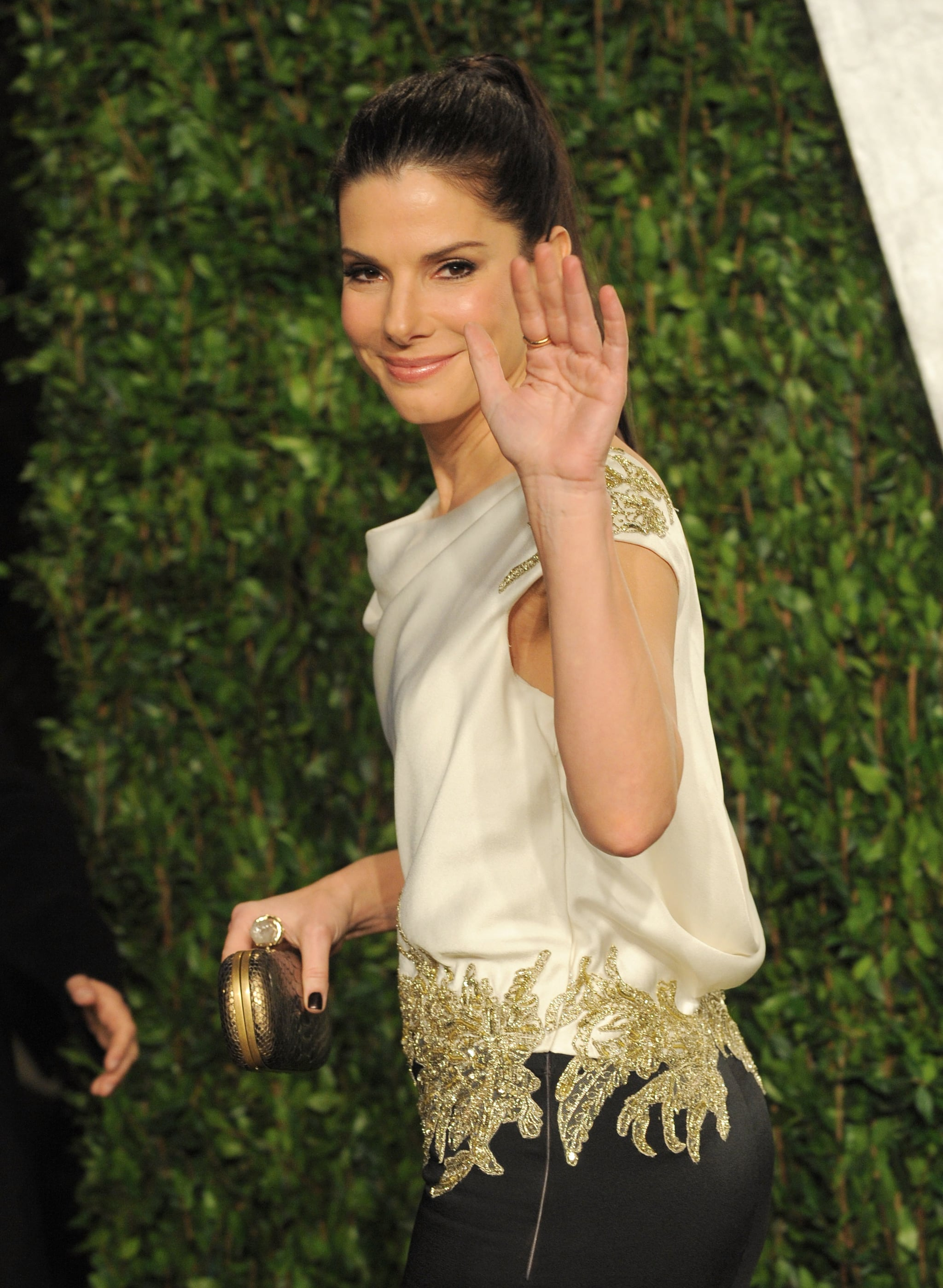 Sandra waves hello to photographers at the Vanity Fair party.