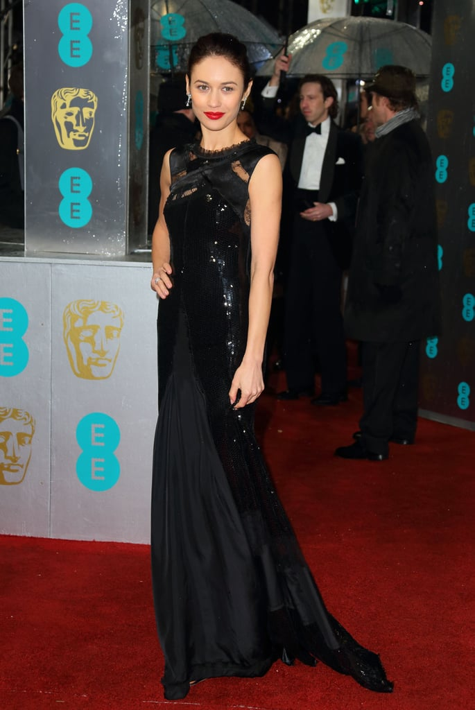 At the British Academy Film Awards in London, Olga Kurylenko chose another black gown, this time with sequin, ruffle, and lace details. Her red lipstick was the perfect finishing touch.