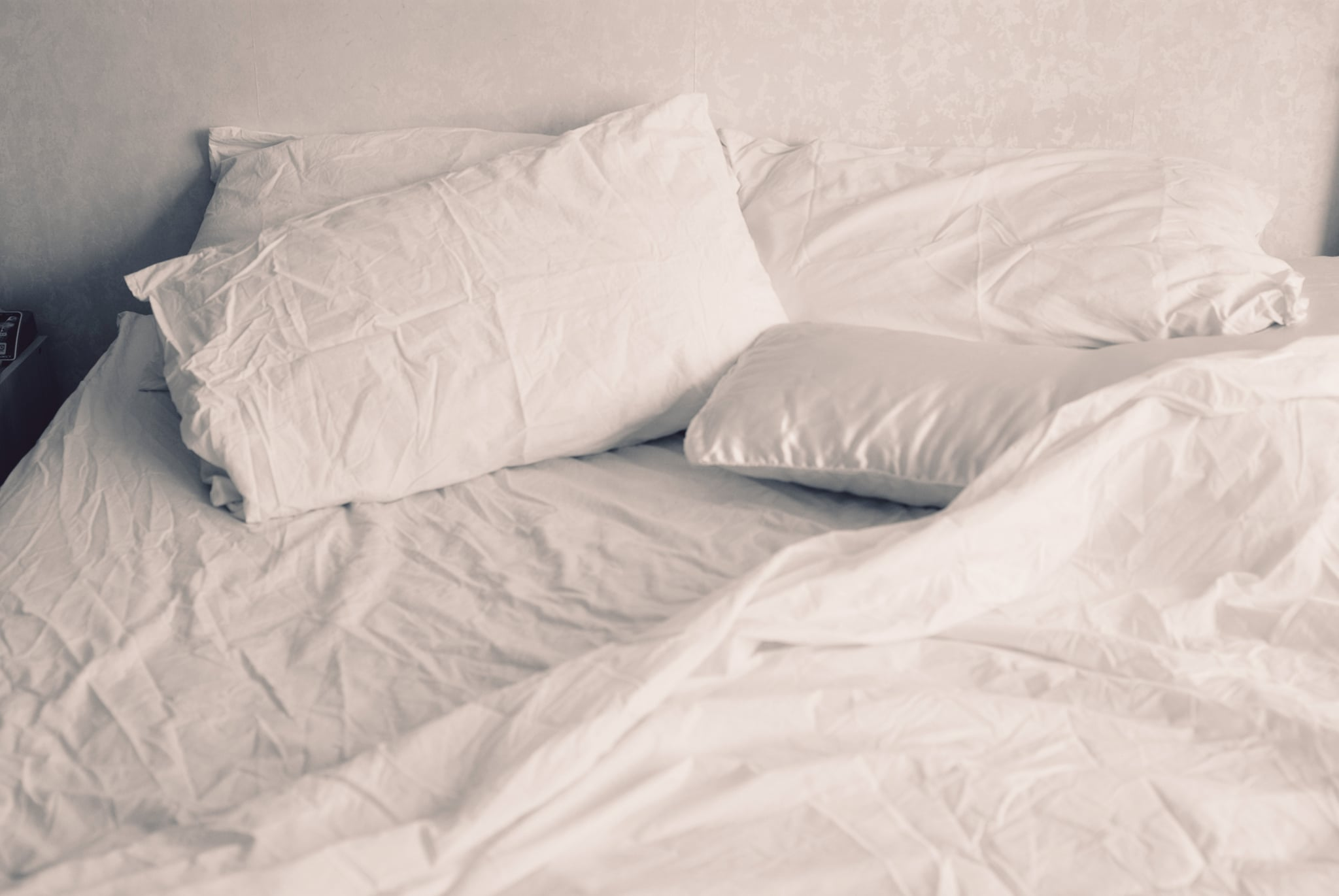 White linen of an unmade bed.
