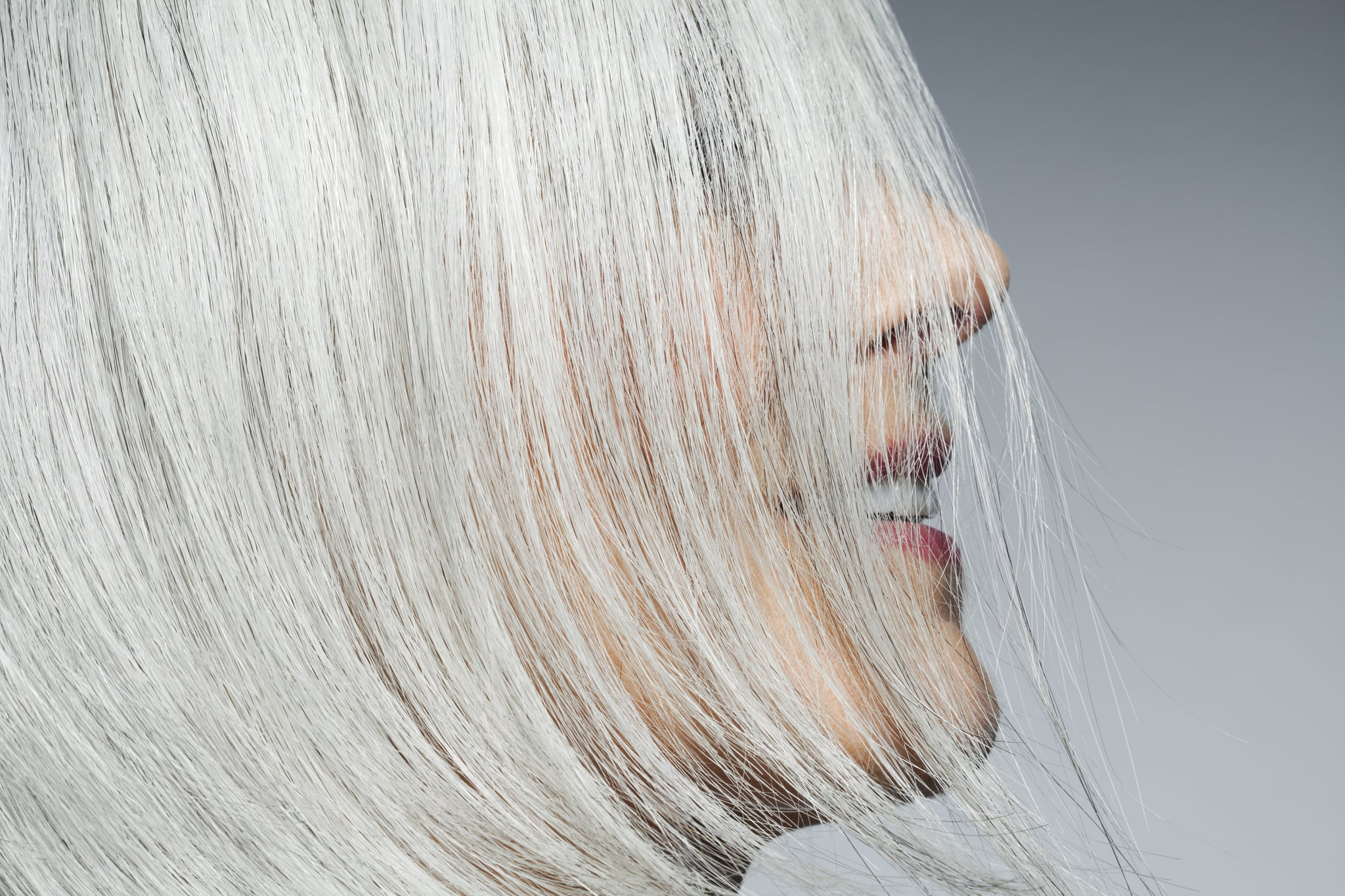 Woman with medium length, silvery, grey hair covering face in front of grey background in a profile position, cropped.