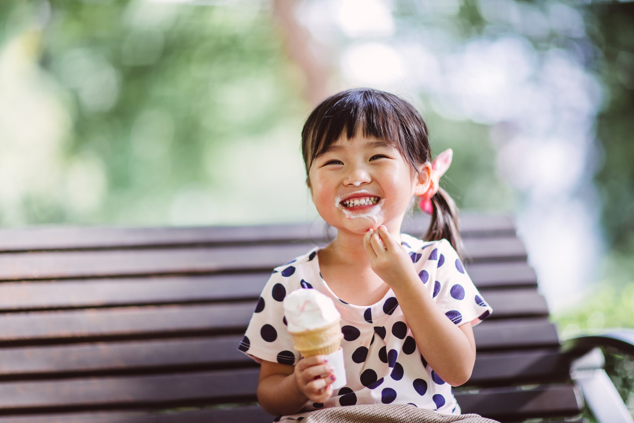 Lovely little girl sitting on the bench having ice-cream cone  in the park joyfully.