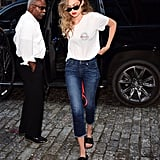 Few outfits are as easy as a white tee and jeans. Gigi Hadid looks extra good thanks to the cropped denim style and black slides (plus a pop of red lipstick).