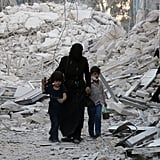 A woman and two children walk through rubble in Aleppo.
