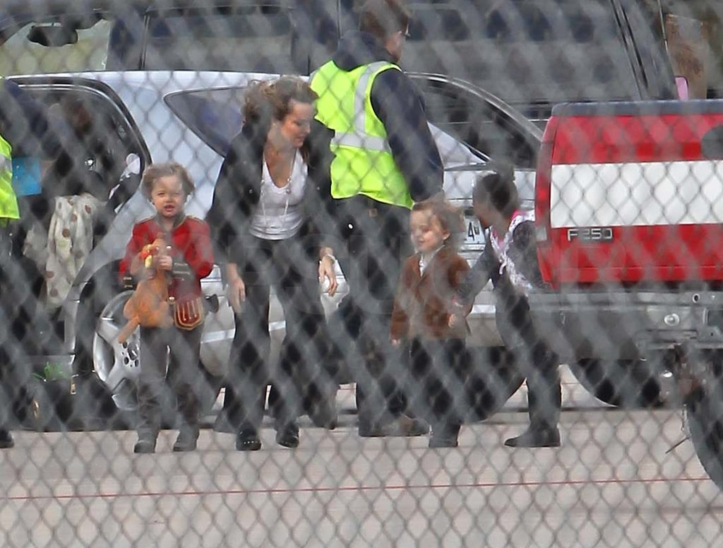Angelina Jolie and Maddox led the way while Shiloh, Knox, and Zahara had a little help boarding a plane in Springfield, MO, today. Shiloh showed off her style in her adorable military jacket, and Knox kept up with a little help from Zahara. The family stopped in Brad Pitt's hometown for a few days after spending Christmas together in Namibia. They're closing out a busy year of traveling around the world, and we can't wait to see what 2011 brings for the adorable family.